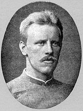 Head and shoulders of a young, fair-haired man with a blond moustache, looking to the right. He is wearing a jacket buttoned to the neck.
