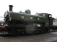 "A pannier tank locomotive is standing over an inspection pit. The locomotive is mainly painted green above the running plate, although the chimney is black and the safety valve cover is polished brass. The letters ""G W R"" are shown in yellow with red shading on the side of the pannier tank. The front buffer beam is painted red."