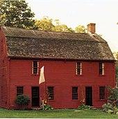 , Casa de dos pisos de madera simple.  Las dos puertas se abren directamente en el jardín delantero.