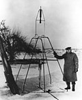 This black and white photo shows Robert Goddard standing next to a frame in which a small (three to four foot) rocket is mounted. It is winter, and open snow-covered fields are in the background.