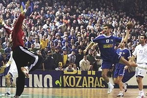 Handball player leaps towards the goal prior to throwing the ball, while the goalkeeper extends himself trying to stop it. This was the Bosnian handball team playing in Visoko against Greece in the qualification for European championship.