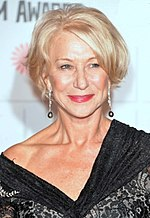 A woman in her late sixties is seen wearing a black dress and earrings.