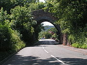 A view along a road, looking through a stone bridge that is partly obscured by trees.
