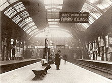 "A black-and-white photograph of a railway station platform under a barrel roof. Several figures are visible, one standing wearing a top hat, a sign reads ""WAIT HERE FOR THIRD CLASS""."