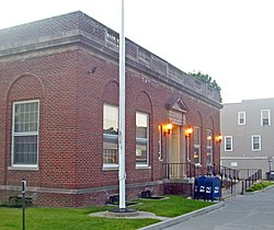 A side view of the front of a brick building with its front lamps on