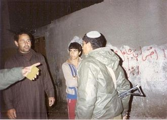 First Intifada - An IDF soldier requesting a resident of Jabalia to erase a slogan on a wall during the first intifada.