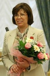 A woman with brown hair, wearing eyeglasses and a tan suit, holding a bouquet of flowers.