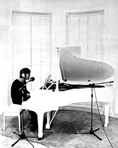 A black and white photo of Lennon sitting at a white parlour grand piano. He is wearing headphones and a dark shirt.