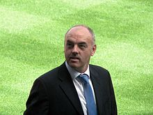 A balding man with a moustache in a suit, looking up, standing on grass.