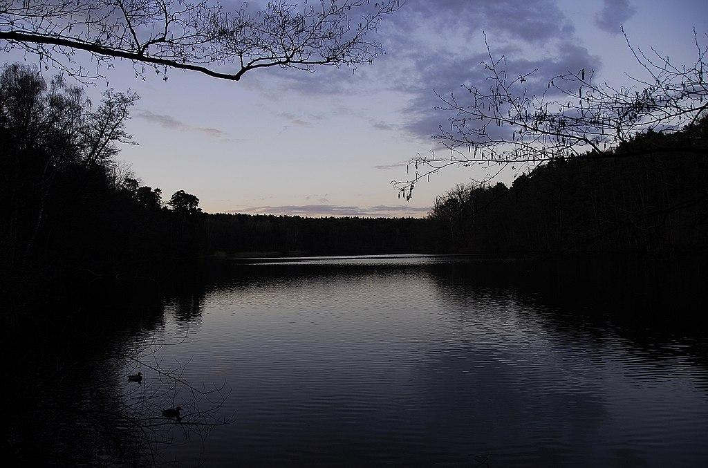 Badesee Krumme Lanke in der Dämmerung. Heller Himmel, der sich auf dem hellen See spiegelt. An den Ufern der dunkle Grunewald.