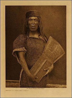 "Kwakwaka'wakw - Man with copper piece, hammered in the characteristic ""T"" shape. Photo taken by Edward S. Curtis."
