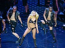 A blond woman wearing a black bustier embellished with shiny crystals performs next to two male back up dancers both wearing black leather jackets embellished with crystals and ripped jean shorts