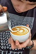 Free pouring of latte art at Doppio Ristretto in Chiang Mai. The artist won several championships in Australia and came in 6th at the world championship in 2011. This is his signature latte art: angel surfing on waves.