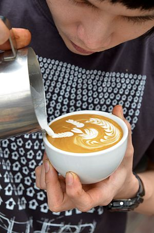 Latte art - The winner of a free-pouring championship creating his signature latte art, that of an angel surfing on waves.