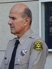 ロサンゼルス郡保安局のリー・バカ保安官(局長)。胸には保安官バッジ、シ... アメリカ合衆国の警