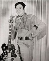A dark-haired man wearing a neckerchief, a shirt with fringes dangling from the sleeves, and pants with a guitar pictured on them, smiling broadly while leaning on a guitar