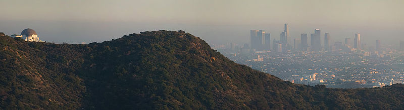 Hills of Griffith Park with smog and downtown L.A. in the background. Griffith Observatory is seen to the left, Downtown Los Angeles in the center.