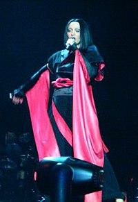 Madonna performing during the Drowned World Tour. She has a short brunette hair wig and wearing a black-and-red kimono. She is singing, while holding a microphone with her left hand
