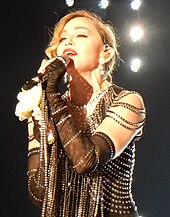 A blond woman dressed in a jeweled dress sings to a microphone