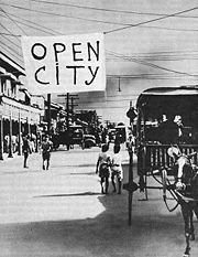 """A Manila street with a large sign hanging over it which reads """"open city"""""""