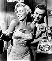 Monroe in The Seven Year Itch. She is holding a bag of chips and wearing a dress, whose shoulder straps are undone. Behind her is Tom Ewell, who is holding the straps.