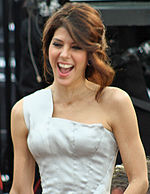 A photo of a brown-haired woman wearing a white dress.