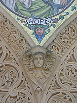 "A carving of the head and wings of an angel: above the angel is the bottom of a mosaic with the label ""HOPE"" and a margin which has a head with flowering ivy."
