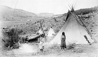 Mescalero - Two Mescalero women, with tipis and ramada (to the left).