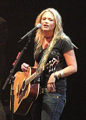 A woman with long blonde hair, wearing a black t-shirt and blue jeans, playing a guitar and singing into a microphone