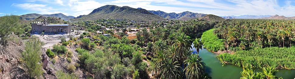 180° Panorama of the Misión Santa Rosalía de Mulegé backed by mountains: La Misión and Santa Clara. The meandering Mulegé River appears on the right lined with palm trees as seen on a sunny December afternoon.