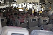 Interior of the aircraft, after the crash, showing oxygen masks hanging from the ceiling, ready for use. The seat backs have video displays installed, and most seats are in position, some reclined, some upright. The overhead compartments are open.