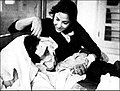 Nargis tends to an injured Sunil Dutt during the filming of Mother India.jpg