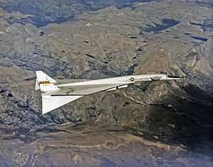 White delta-wing aircraft overflying mountains. At the front of aircraft are canards. Tips of wings are drooped down.