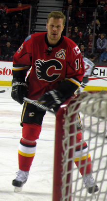 "A man with short hair stares forward. He is in full hockey gear and wearing a red uniform with yellow, white and black trim and a stylized ""C"" logo on the chest"