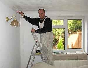 A painter painting a room in a house