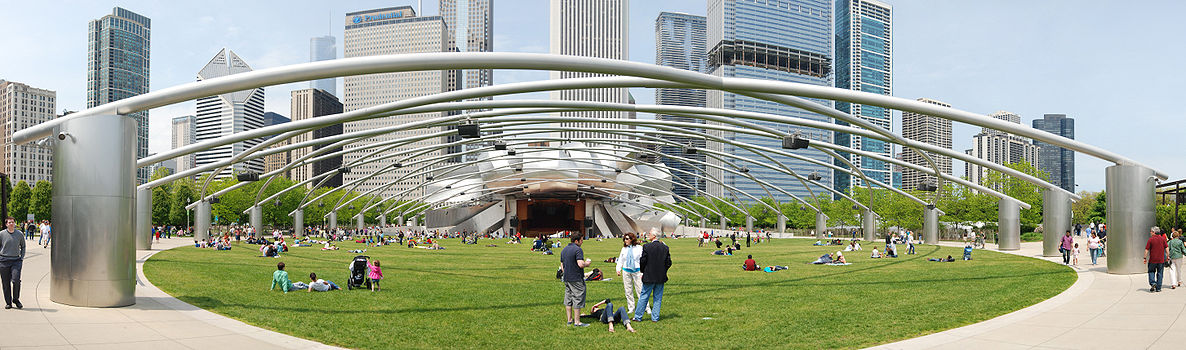 Futuristic view of a green lawn with people scattered on it, beneath a metal trellis supported on shiny metal pillars. The trellis leads to a bandshell surrounded by curved plates of shiny metal, with many tall skyscrapers in the background.