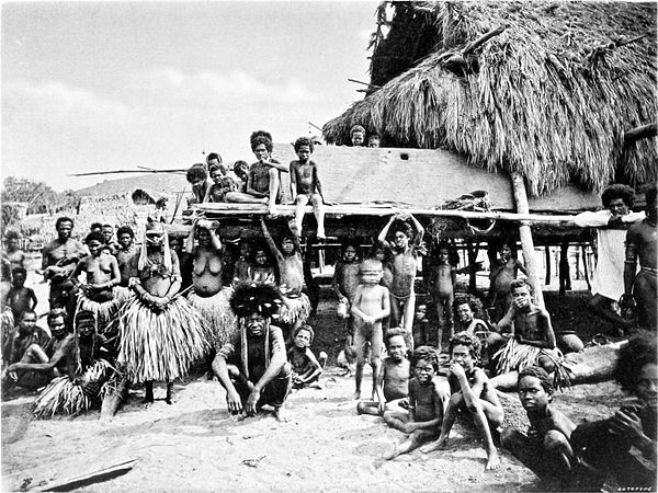Black and white photograph of a large group of people, sitting and standing, mostly women and children, with little clothing. A thatched, log building in the background.