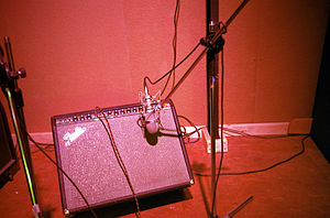 "Instrument amplifier - A Fender ""combo"" amplifier. The combination amplifier is a preamplifier, power amplifier and tone controls and one or more loudspeakers or drivers mounted in a portable wooden cabinet. This amp's sound is being picked up with a microphone in a recording studio."