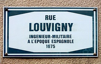 """Fortress of Luxembourg - Street sign for Rue Louvigny. The explanation reads """"Military engineer in the Spanish period, 1675""""."""