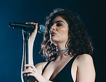 A young Caucasian woman with shoulder-length, curly, dark hair wearing two choker chains, a necklace, a revealing black dress and a ring holds a stand-mounted microphone.