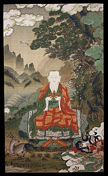 Elderly monk in green and red robes, holding his hands in front of his chest.