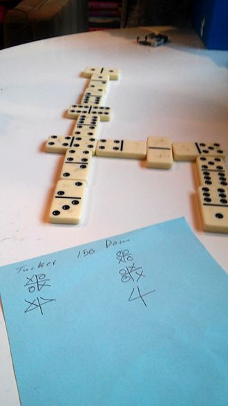 Dominoes - Score being kept by houses: The player at left has 75 points and the player at right has 115 points.