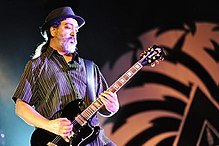 A male electric guitarist, Kim Thayil, onstage with an electric guitar. He has a beard.