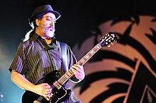 Um guitarrista do sexo masculino elétrico, Kim Thayil, no palco com uma guitarra elétrica.  Ele tem uma barba.