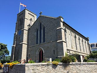 Isles of Scilly - The Scillonian Cross flying above St Mary's Church in Hugh Town.