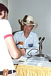 Man in a cowboy hat and white shirt with thin blue stripes sitting at a table with a microphone