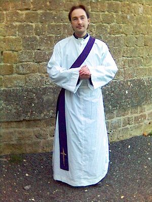 Alb - An Anglican cleric vested as a deacon, with alb and cincture and a purple stole.