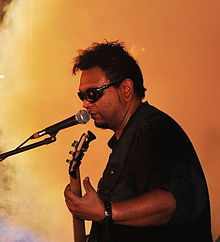 Man in dark glasses onstage, playing guitar and singing