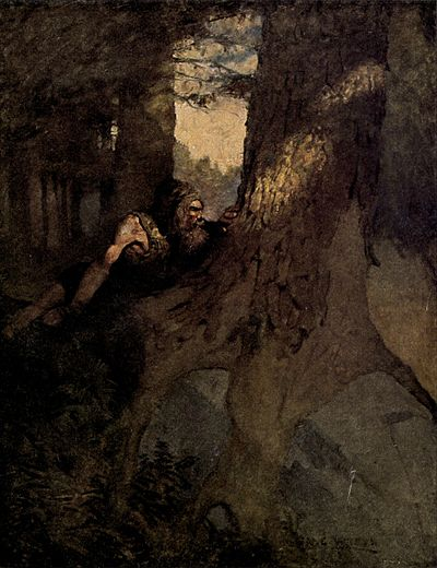 A bearded man hides behind the trunk of a large tree, watching events outside the frame of the image.