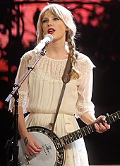 Taylor Swift performing live on a banjo, wearing a beige blouse and pigtails